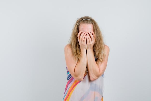Блондинка в летнем платье держится за руки на лице и выглядит расстроенной