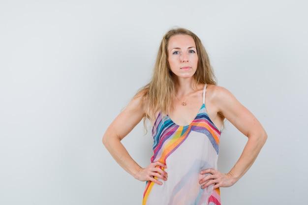 Блондинка в летнем платье держится за талию и выглядит уверенно