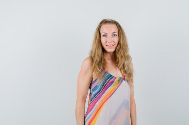 Блондинка в летнем платье смотрит в камеру и выглядит оптимистично