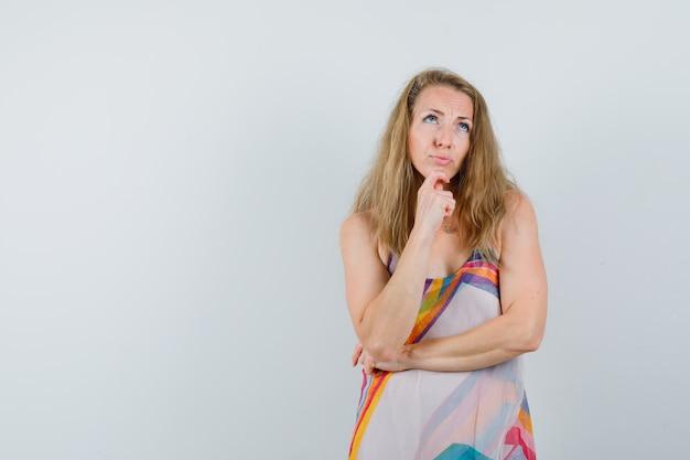 Блондинка в летнем платье смотрит вверх с пальцем на подбородке и выглядит задумчиво