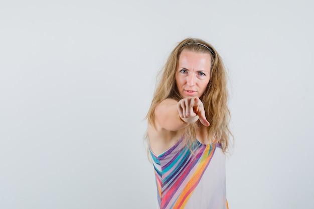 Блондинка в летнем платье показывает пальцем на камеру и выглядит решительно
