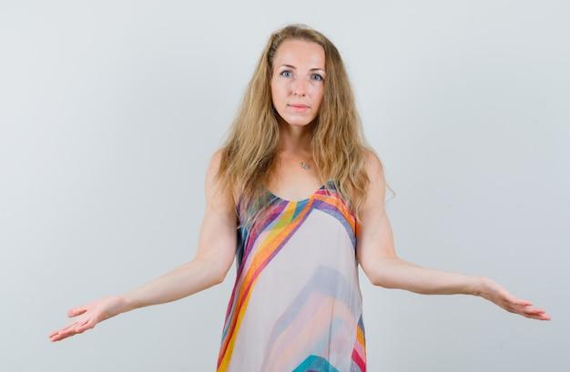 Блондинка в летнем платье показывает беспомощный жест и выглядит смущенным