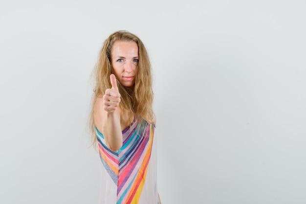 Блондинка в летнем платье показывает палец вверх и выглядит веселым.