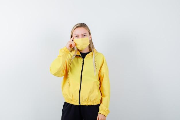 トラックスーツを着た金髪の女性、こめかみに指を保持し、賢明に見えるマスク、正面図。