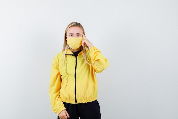 トラックスーツを着た金髪の女性、こめかみに指を保持し、真剣に見えるマスク、正面図。