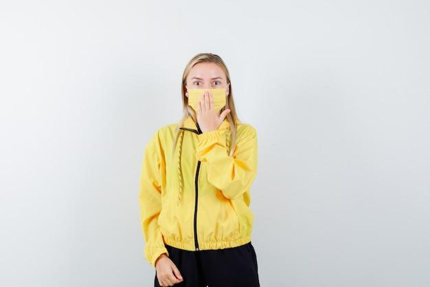 Блондинка в спортивном костюме, маска держит руку на рту и выглядит испуганной, вид спереди.