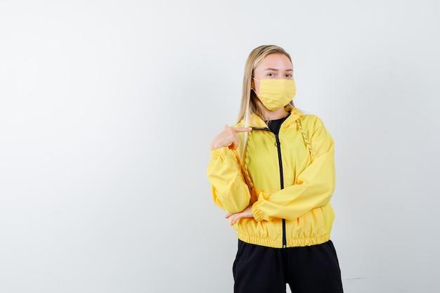 Блондинка в спортивном костюме, маска указывает на себя и выглядит гордо, вид спереди.