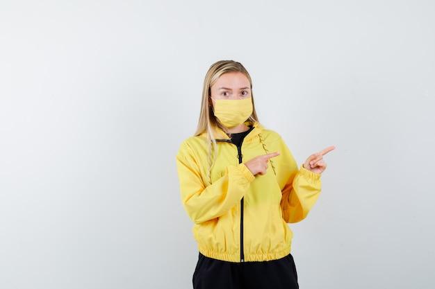 Блондинка в спортивном костюме, маска указывает вправо и выглядит озадаченным, вид спереди.