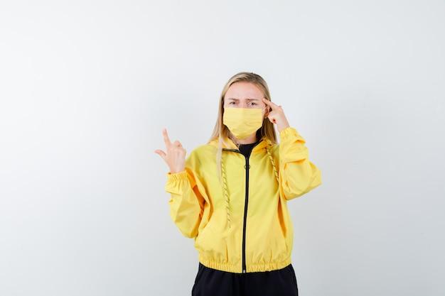 Блондинка в спортивном костюме, маска указывает вверх, держит палец на висках и выглядит озадаченным, вид спереди.