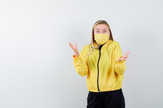 トラックスーツを着た金髪の女性、無力なジェスチャーを示し、混乱しているように見えるマスク、正面図。