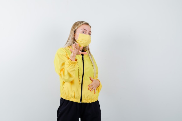 トラックスーツを着た金髪の女性、停止ジェスチャーを示し、焦点を合わせて見えるマスク、正面図。