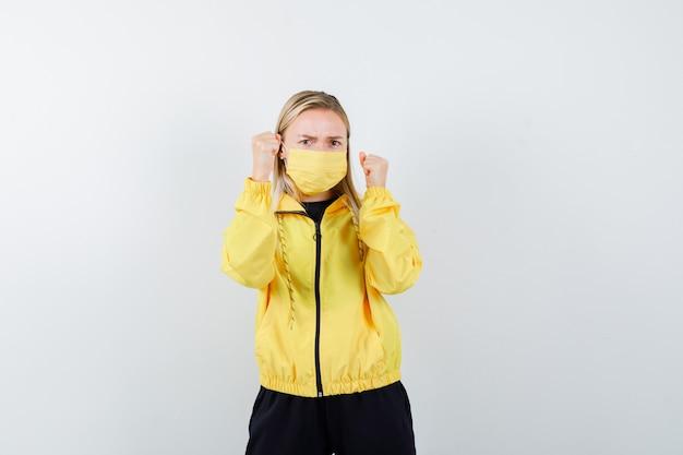 トラックスーツを着た金髪の女性、勝者のジェスチャーを示し、真剣に見えるマスク、正面図。