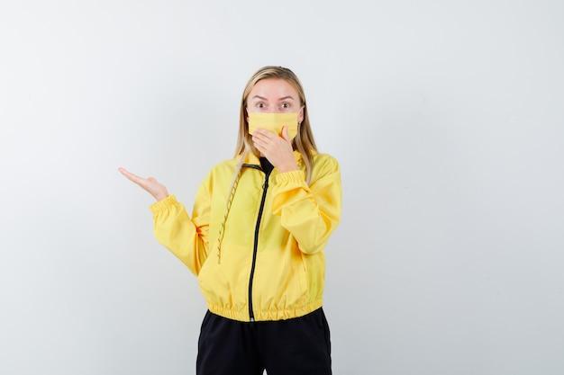 Блондинка в спортивном костюме, в маске раздвинула ладонь, держит руку у рта и выглядит потрясенной, вид спереди.