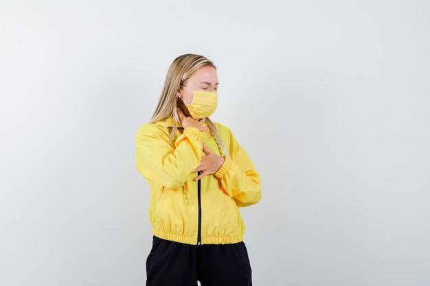トラックスーツを着た金髪の女性、喉の痛みに苦しんでいるマスク、病気に見える、正面図。