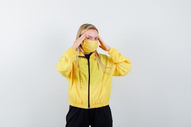 トラックスーツを着た金髪の女性、強い頭痛に苦しんでいるマスク、疲れているように見える、正面図。