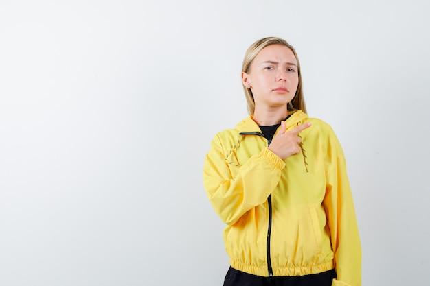 Блондинка в спортивном костюме, указывая на верхний правый угол и нерешительно глядя, вид спереди.