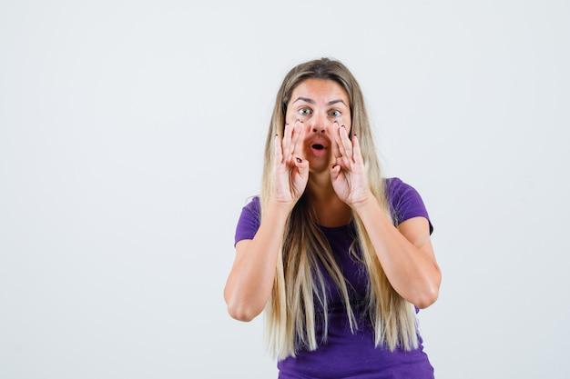 口の近くの手で秘密を告げる紫のtシャツの金髪の女性、正面図。