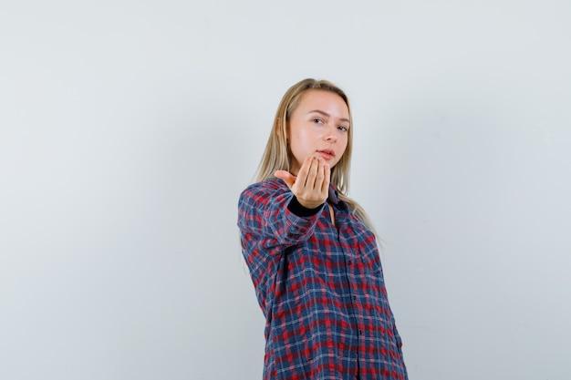 カジュアルなシャツに誘い、自信を持って見える金髪の女性。正面図。