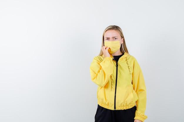 Signora bionda tenendo la mano sulla guancia in tuta da ginnastica, maschera e guardando ansioso, vista frontale.