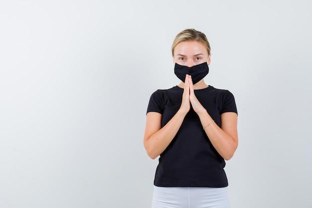 고립 된 검은 티셔츠에 제스처를기도에 손을 유지 금발 아가씨