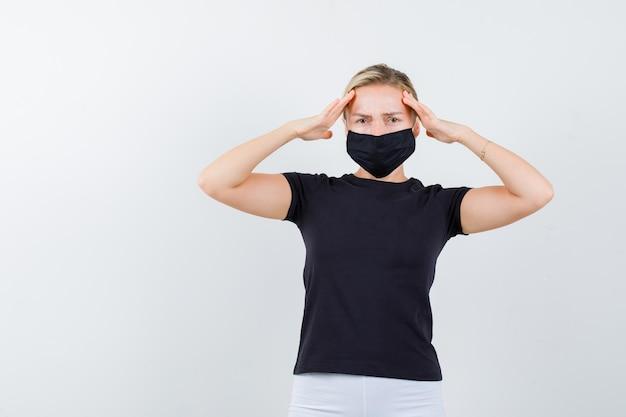 금발 아가씨는 검은 색 티셔츠, 검은 마스크로 머리에 손을 얹고 고통스러워 보입니다.