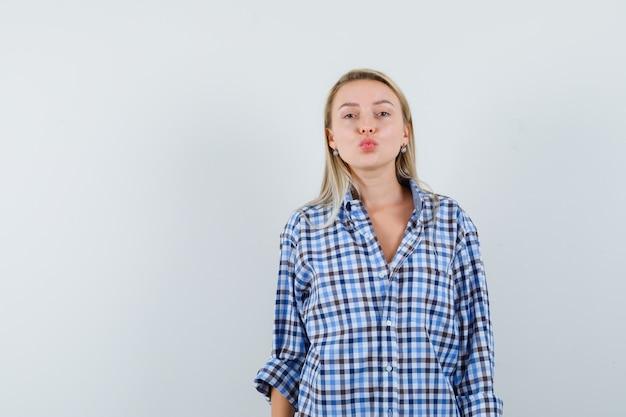 チェックのシャツに唇を折りたたんで見栄えの良いブロンドの女性