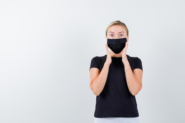 Signora bionda che tiene le mani alzate vicino al viso in maglietta nera, maschera nera isolata