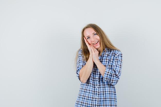 금발 아가씨 셔츠에 베개로 손바닥에 기대어 귀여운 찾고,