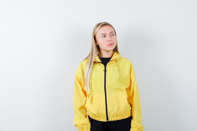 Blonde lady looking aside in tracksuit and looking thoughtful. front view.