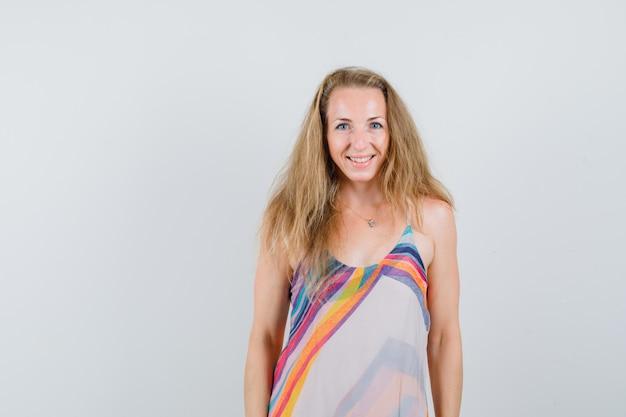 Блондинка смотрит в камеру в летнем платье и радостно смотрит.