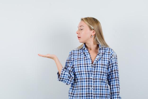 Блондинка смотрит на ее раздвинутую ладонь в повседневной рубашке