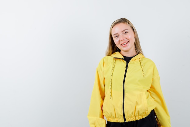 Blonde lady looking at camera in tracksuit and looking merry , front view.