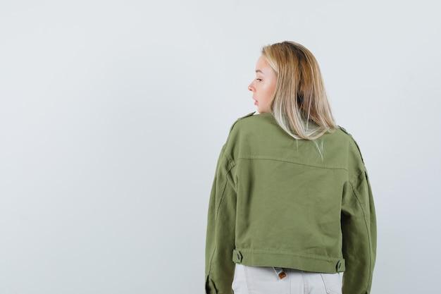 ジャケット、パンツ、自信を持って彼女の肩越しに見ているブロンドの女性。背面図。
