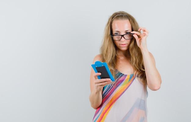 Блондинка, просматривая заметки в буфер обмена в летнем платье
