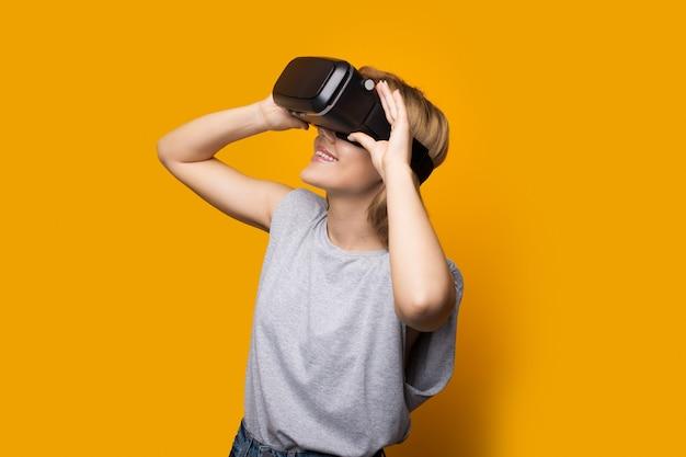 Блондинка смотрит на что-то с помощью гарнитуры виртуальной и дополненной реальности