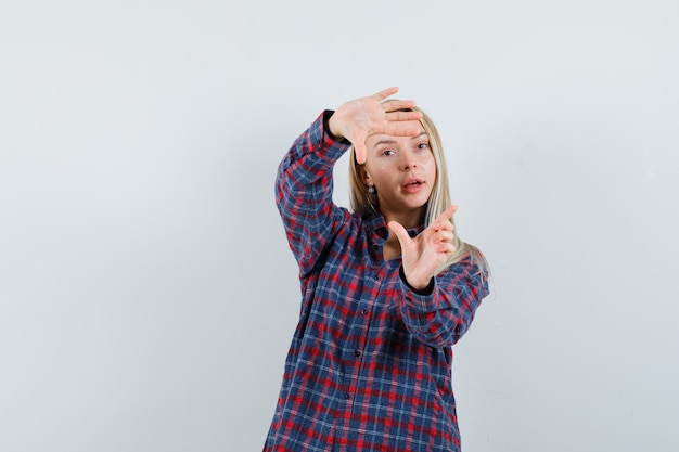 Signora bionda che fa il gesto del telaio in camicia casual e che sembra sicura. vista frontale.