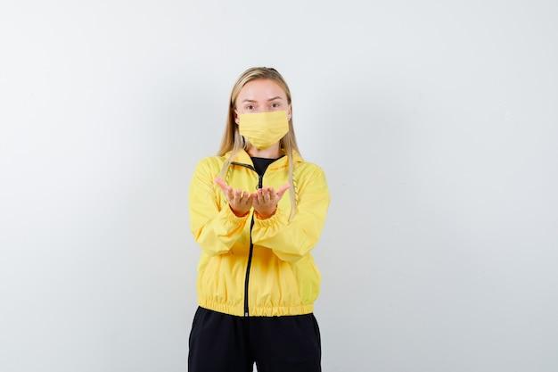 금발 아가씨는 운동복, 마스크에서 제스처를주고받는 부드러운 찾고 있습니다. 전면보기.