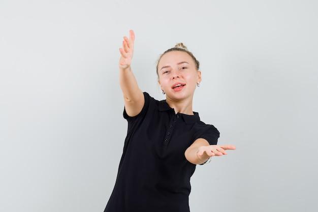 Блондинка раскрывает руки для объятий в черной футболке и выглядит счастливой. передний план.