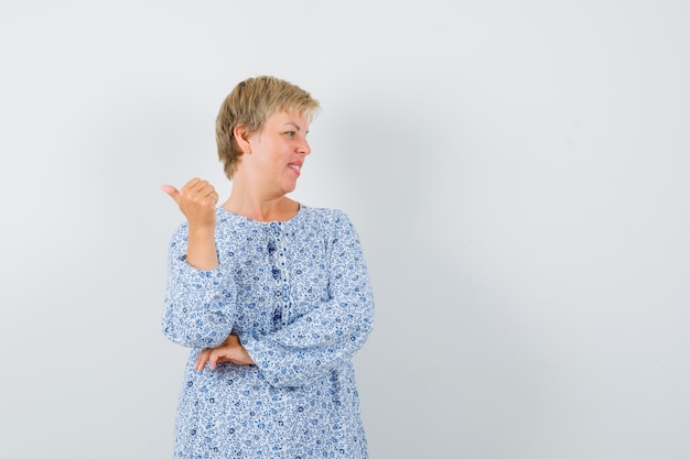 Blonde lady in patterned blouse pointing back , front view. space for text
