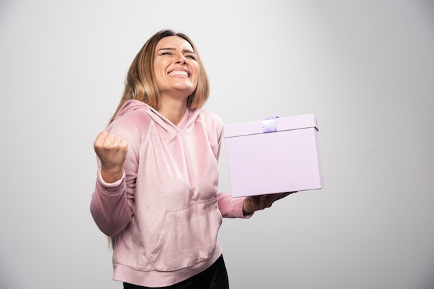 Blonde lady in pink sweatshirt holds a gift box and looks very happy.