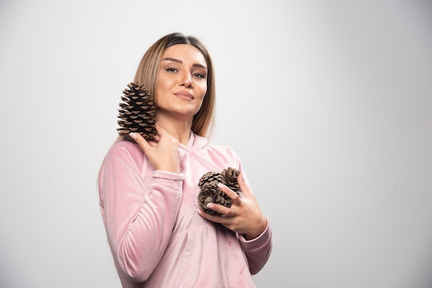 Blonde lady in pink sweatshirt makes positive and happy face by holding oak tree cones.
