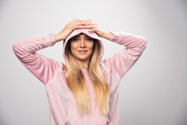 Blonde lady in pink sweatshirt making joyful and positive poses by wearing hoodie to her head.
