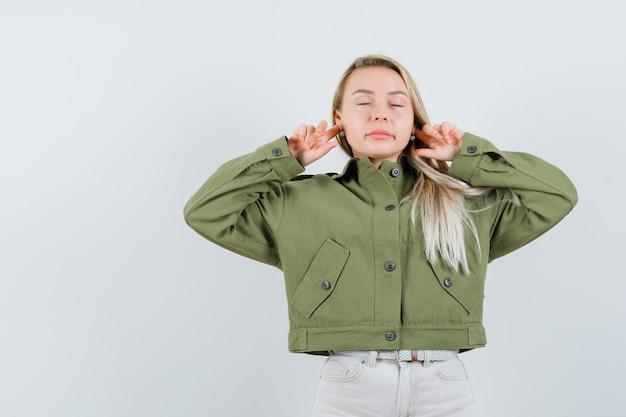 Signora bionda che collega le orecchie con le dita in giacca, pantaloni e sembra rilassata. vista frontale.
