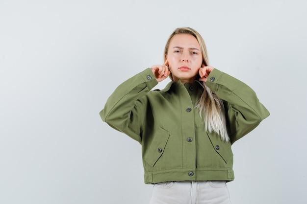 Signora bionda che collega le orecchie con le dita in giacca, pantaloni e sembra stanca. vista frontale.