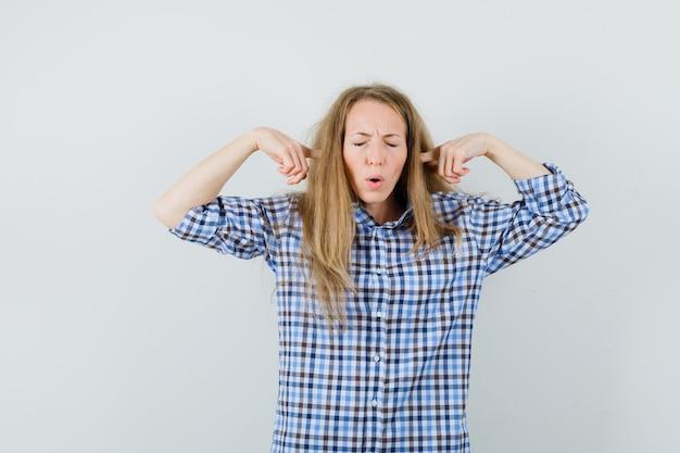 Signora bionda tappando le orecchie con le dita in camicia e guardando infastidito,