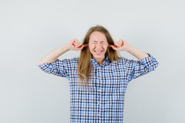 Signora bionda tappando le orecchie con le dita in camicia e guardando irritata,