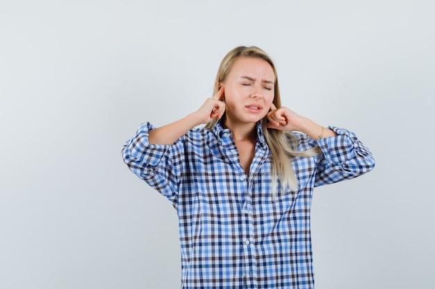 Signora bionda tappando le orecchie con le dita in camicia a quadri e guardando infastidito