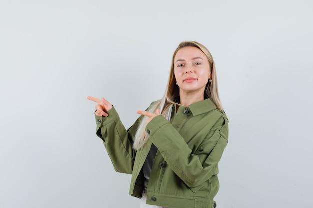 Блондинка, указывая в сторону в куртке, штанах и уверенно глядя, вид спереди.