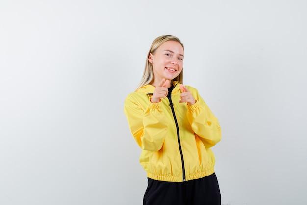 Блондинка, указывая на камеру в спортивном костюме и весело глядя, вид спереди.