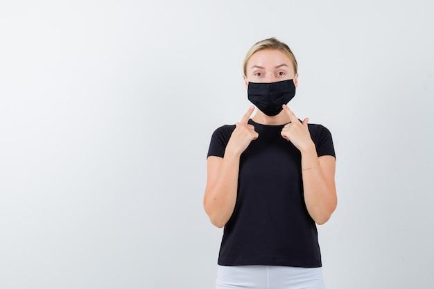 Блондинка, указывая на ее медицинскую маску в черной изолированной футболке